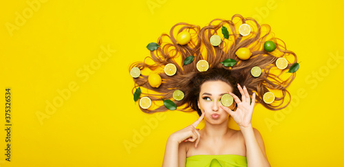 Fotografie, Obraz positive girl lying on yellow background with citrus fruits in long hair,young w