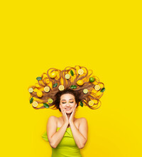 Dreamy Girl Lying On Yellow Background With Citrus Fruits In Long Hair,young Woman Head With Lemon Slices And Leaves,