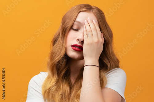 Photo Photo of tired girl with wavy redhead, covers face hand, feels fatigue, needs go