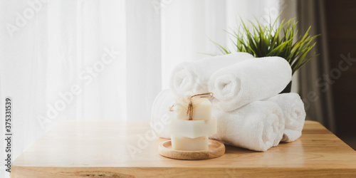 Fotografering White  soft folded towels and organics soap on wood table with blurred white bat