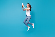 Full Length Body Size View Of Her She Attractive Pretty Slim Fit Funky Cheerful Girl Blogger Jumping Having Fun Using Cell App 5g Fast Speed Isolated Bright Vivid Shine Vibrant Blue Color Background
