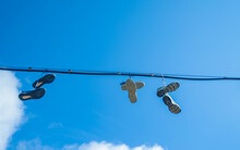 Sneakers Hang On Wires Against...