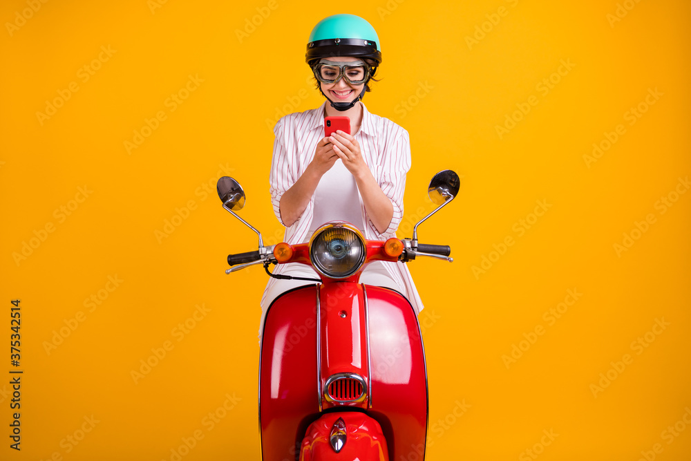 Fototapeta Photo of positive girl ride drive scooter use smartphone search location destination online wear white striped shirt trousers goggles helmet isolated bright shine color background