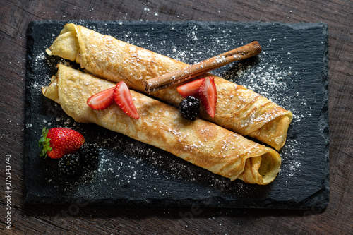 Top view of appetizing crepes dessert on dark tile #375343748
