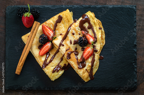 Top view of crepes dessert with chocolate and red fruit dressing #375343775