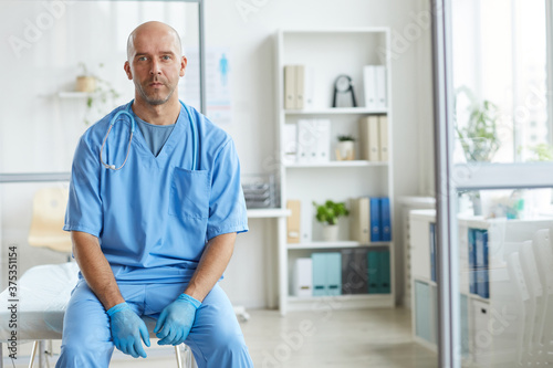 Fotografie, Obraz Portrait of modern man wearing blue uniform working in hospital sitting in his o