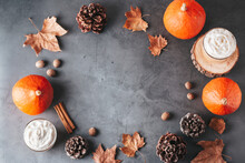 Autumn Frame With Natural Pine Cones, Pumpkins, Dried Leaves And Pumpkin Latte On Dark Grey Stone Top, Top View, Copy Space. Fall, Thanksgiving Background, Cozy Flat Lay
