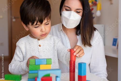 Tela Preschooler Kid playing with wood blocks and teacher educador help using face mask for coronavirus pandemic