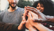 canvas print picture - Young happy people stacking hands outdoor - Diverse culture students celebrating together - Focus on hands