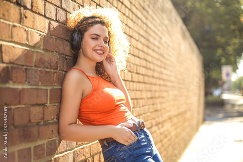 Curly hair girl chilling in the street, lying on a brick wall and listening musi Wallpaper Mural
