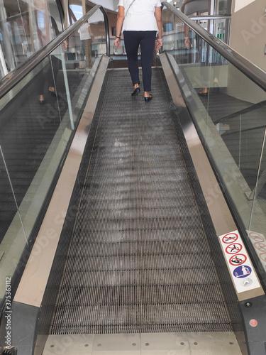 Mujer subiendo por una rampa mecánica Wallpaper Mural