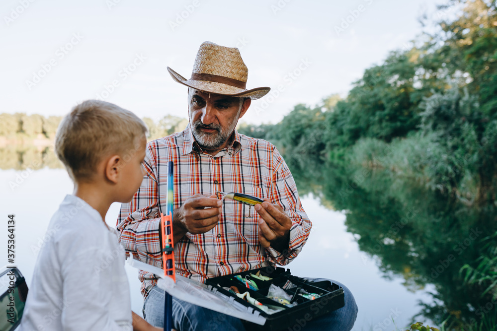 Fototapeta grandfather and grandson fishing outdoor on the lake