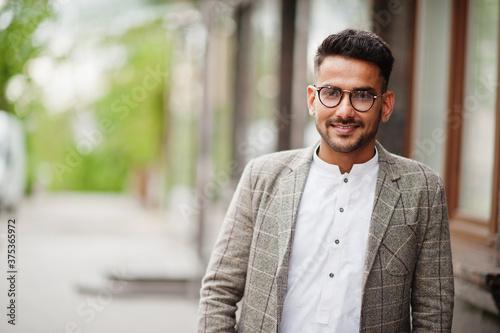 Obraz Stylish pakistani man wear in eyeglasses and jacket. - fototapety do salonu