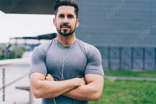 Fotografering Half length portrait of handsome male athlete with muscular figure listening mus