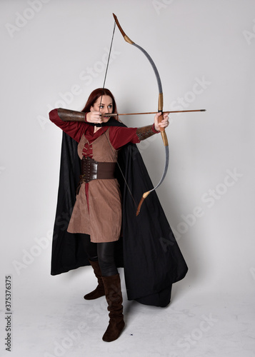 Canvas Full length portrait of girl with red hair wearing medieval archer costume with black cloak