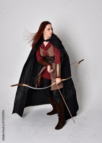 Murais de parede Full length portrait of girl with red hair wearing medieval archer costume with black cloak