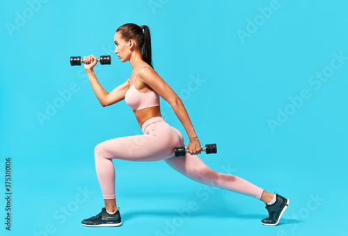 Sporty woman doing lunges exercises with dumbbells Fototapet