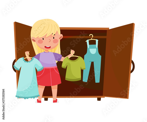 Fotografia Smiling Girl Engaged in Housework Putting Clothing in Wardrobe in Order Vector I
