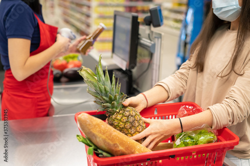 Photo Unrecognizable woman wearing protective mask putting things into shopping basket