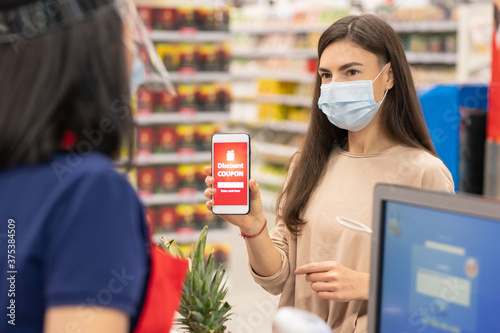 Modern woman wearing mask on face using digital discount coupon on her smartphone in supermarket #375384509