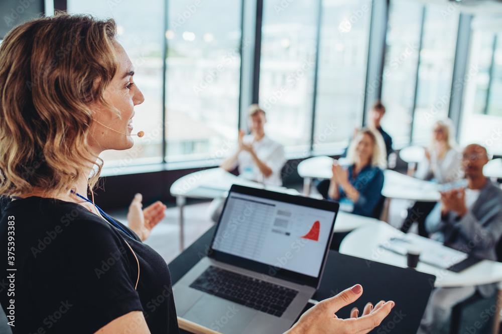 Fototapeta Businesswoman addressing to group of professionals