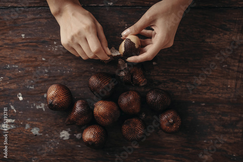 Obraz Close up brown fresh Salacca zalacca Salak snake fruit in held by a woman's hand with natural finger nails on the wooden table in Bali, Indonesia - fototapety do salonu