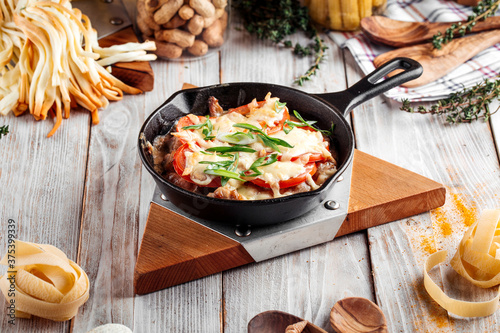 Valokuvatapetti Chicken with tomatoes and cheese in cast iron pan
