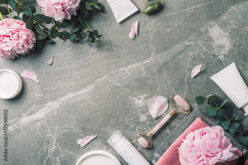 Facial roller, gua sha massager, oil bottle, towel, pink peonies on marble background. Copy space. Flat lay. Top view. Routine facial skin care, body treatment, spa concept.