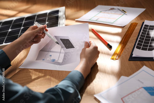 Woman working on house project with solar panels at table in office, closeup Canvas Print