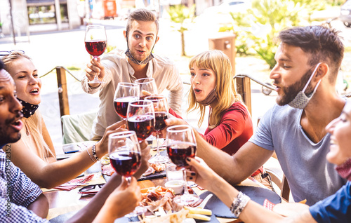 Foto Friends toasting red wine at restaurant bar with face masks - New normal friends