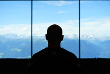 Silouette Of A Bald Man Watching The Mountain From The Window Of An Alpine Refuge