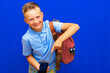 Leinwandbild Motiv Smiling schoolboy in casual clothes backpack Point index finger on mobile phone