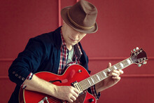 Bluesman With A Guitar. A Musician In A Hat With An Electric Guitar. The Photo Is Tinted In A Retro Style.