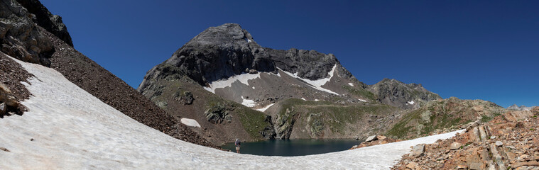 Arratille mountain lake mirror with white snow, and dark blue sky in French High Pyrenees, Pyrenees National Park, France, Europe