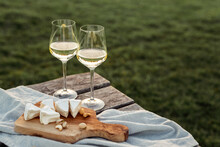 Two Glasses Of White Wine And Wooden Plate With Cheese And Nuts During Sunset Time Outside.