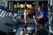 canvas print picture - Personal trainer motivates client doing push-ups in gym.