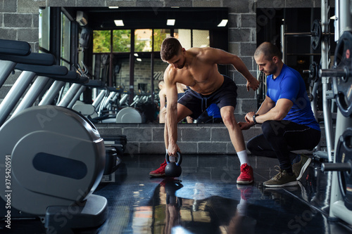 Cuadros en Lienzo Personal trainer motivates client doing push-ups in gym.
