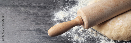 Photo Dough with rolling pin and flour on table, closeup