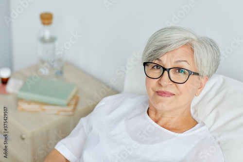 Portrait of Caucasian mature woman wearing eyeglasses recovering in hospital war Canvas