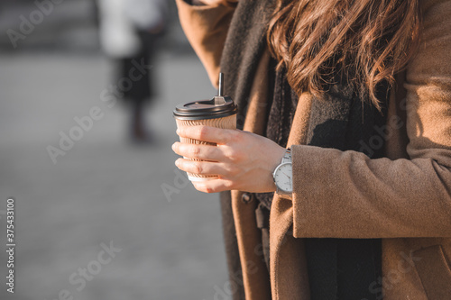 Fotografie, Obraz woman outdoors check time on wrist watch holding paper coffee cup
