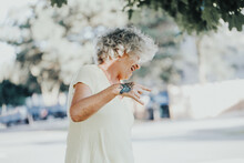 Cool Edgy Caucasian Old Lady Woman With Butterfly Tattoo On Hand. Beautiful Funky Elderly Woman With Grey Hair Making Devil Rock Sign With Fingers. Young At Heart Senior Person.