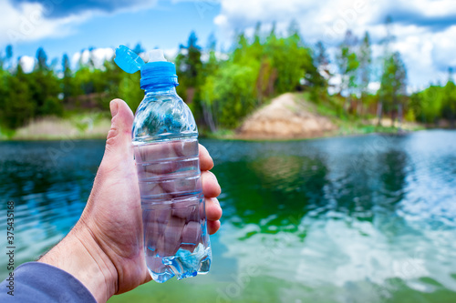 Fotografiet A man's hand holds a water bottle close-up against the background of clear water of a lake with a turquoise hue with the shore in the distance