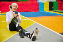 Old Cheerful Lady On A Colourfull Square Outdoors