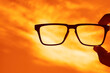 canvas print picture - Hipster male Hand Hold Glasses without glass above yellow sunset  cloudy Sky background. no temples