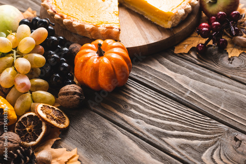 Fotografija autumnal decoration and pumpkin pie on brown wooden background