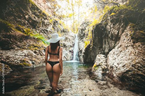 Photo Ragazza con costume nero e cappello bianco in una vasca di fronte una cascata tr