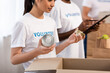 canvas print picture - Selective focus of asian volunteer holding tin cans near cardboard box in charity center