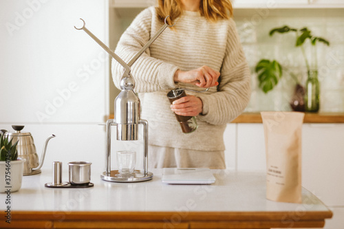Vászonkép Woman grinding coffee at home by manual coffee grinder