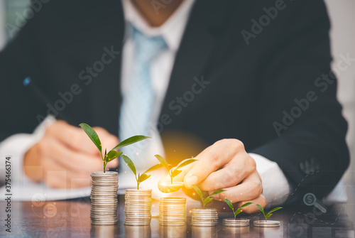Fotografie, Obraz Businessman touch coins with line connect and Coins stack on the wooden table ,