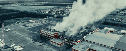 Obraz na plátně Aerial view of fire in burning industrial factory building with big smoke, copy space for text